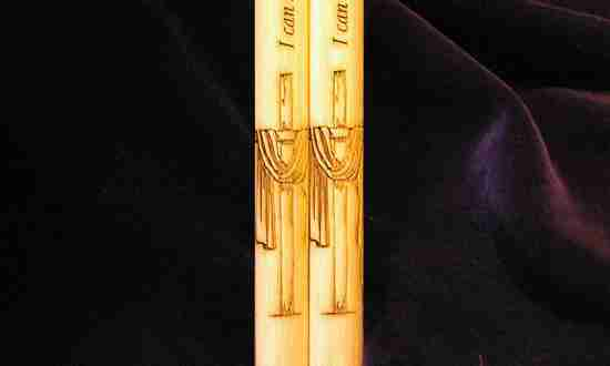 A pair of personalized drumsticks with a cross design engraved and wording