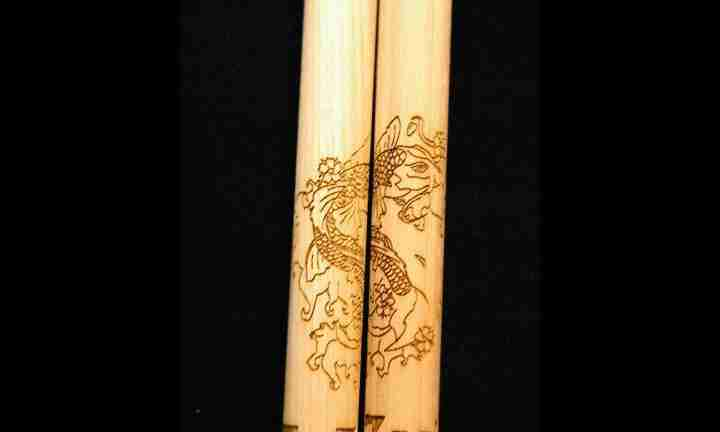 Extremely detailed koi fish graphic engraved on a pair of drumsticks