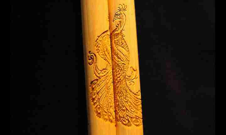 Detailed custom peacock graphic engraving on personalized drumsticks