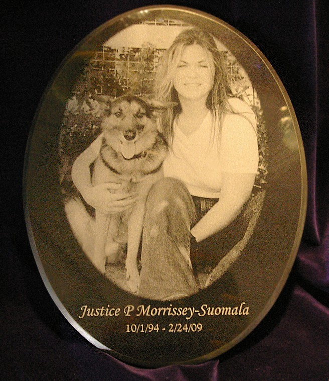 Oval black marble plaque with woman and her dog photo engraved and cropped into oval shape